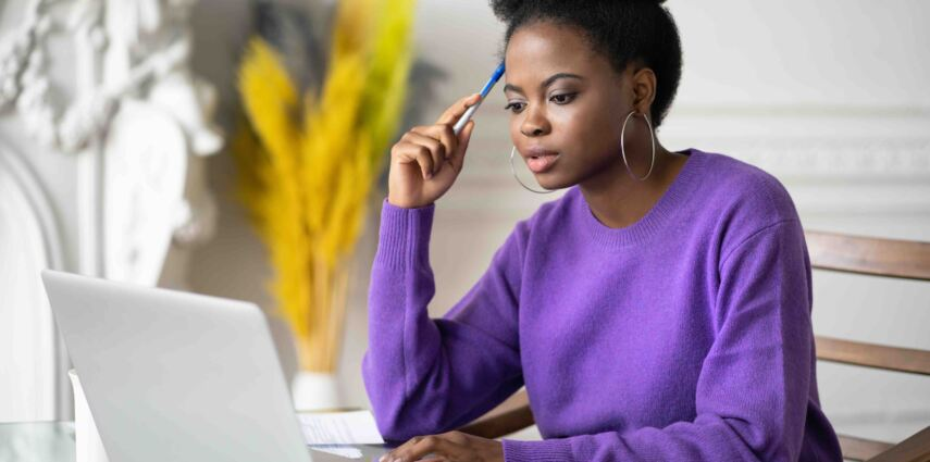 Afro-American millennial student woman with afro hairstyle browsing information on laptop, preparing for exam online, watching video course, holding a pen. Online education in zoom app, video training
